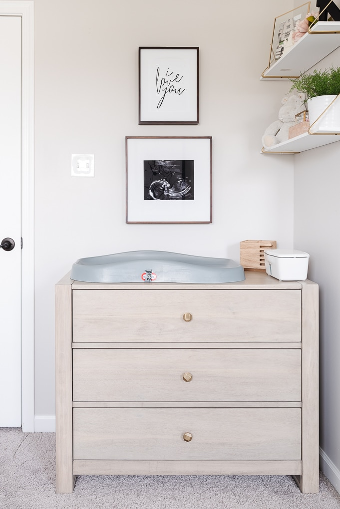 changing table dresser in a modern nursery with artwork on the wall