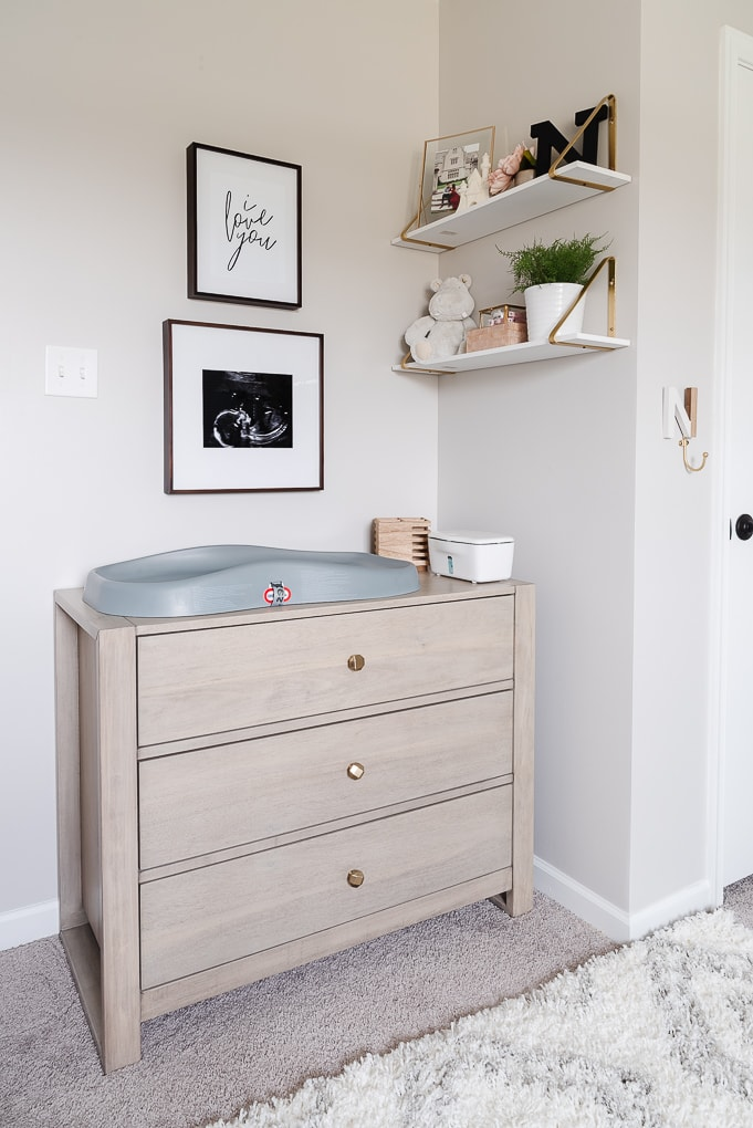 changing table dresser in a nursery with decorative shelves