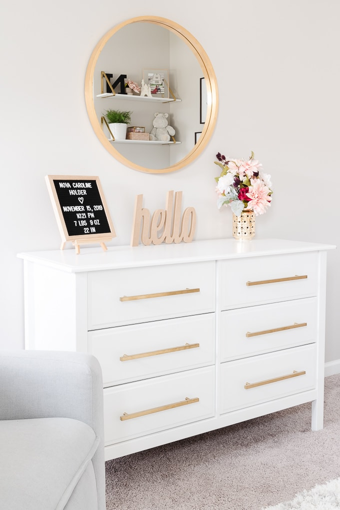 white dresser with modern gold pulls in nursery