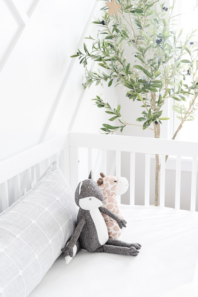 stuffed animal fox and giraffe inside white crib in modern nursery