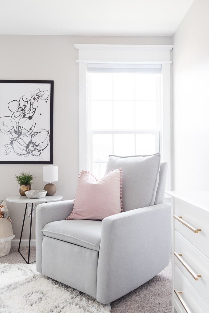 paxton glider from west elm in neutral nursery with pink accent pillow