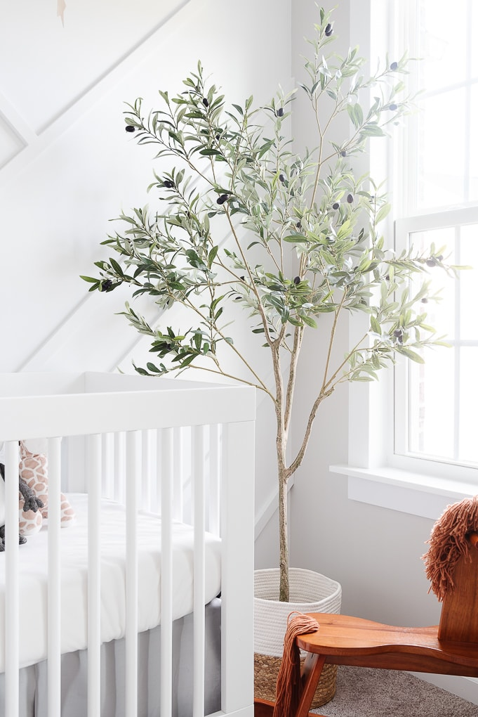 pretty faux olive tree in a basket in a neutral baby nursery