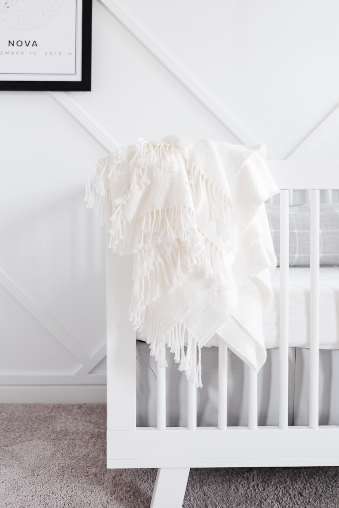 white blanket draped over the side of a white crib
