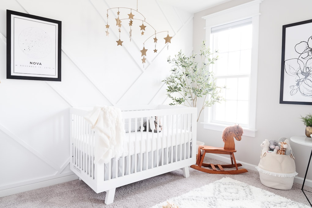 babyletto hudson crib in white against a white accent wall in a nursery