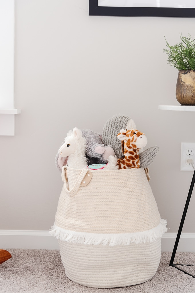 pink soft basket of stuffed animals in a nursery