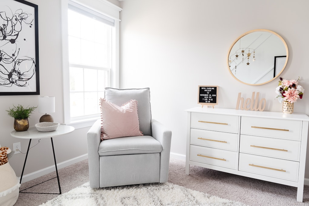 paxton glider chair from west elm in a nursery next to a white dresser