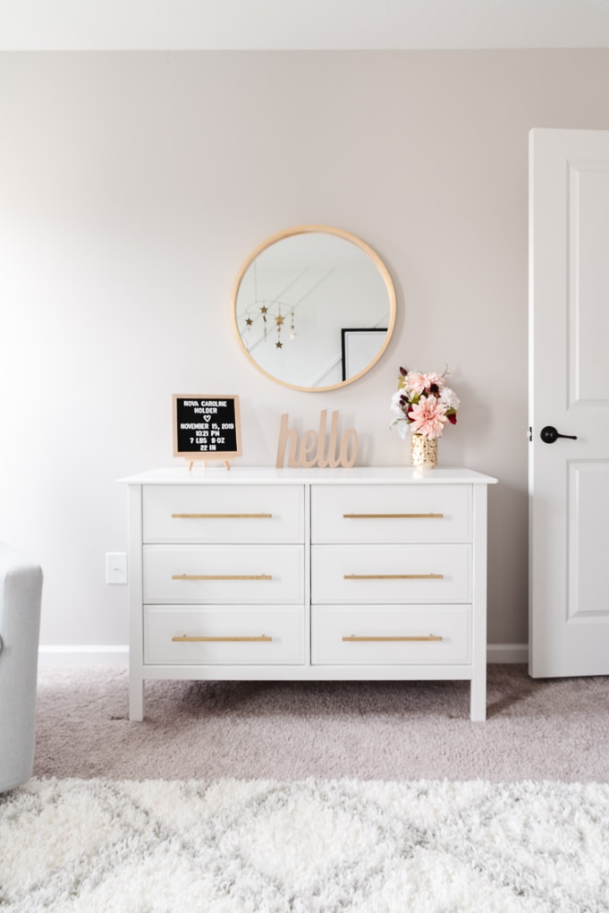white dresser with modern gold pulls and a gold circle mirror in nursery