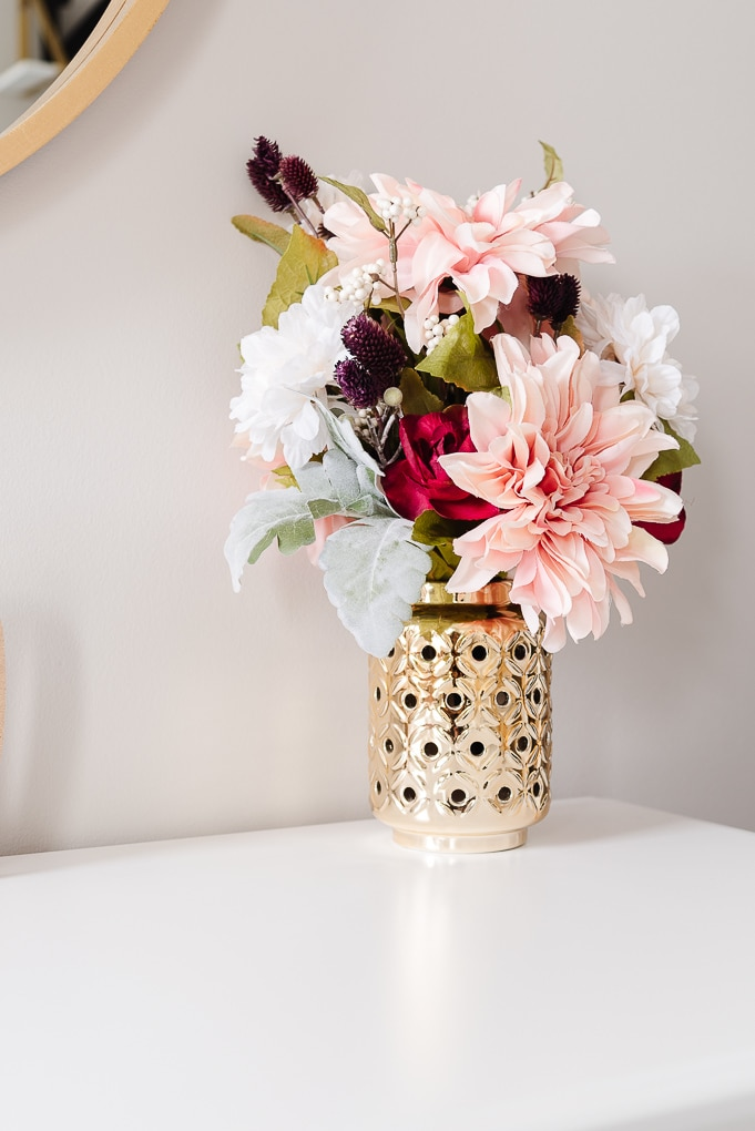 faux floral bouquet in a gold vase in a nursery
