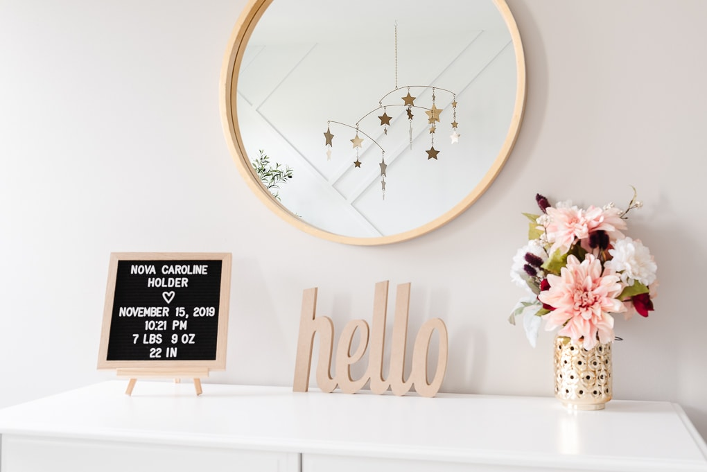 decorative accessories on a nursery dresser with a star mobile reflecting in the mirror