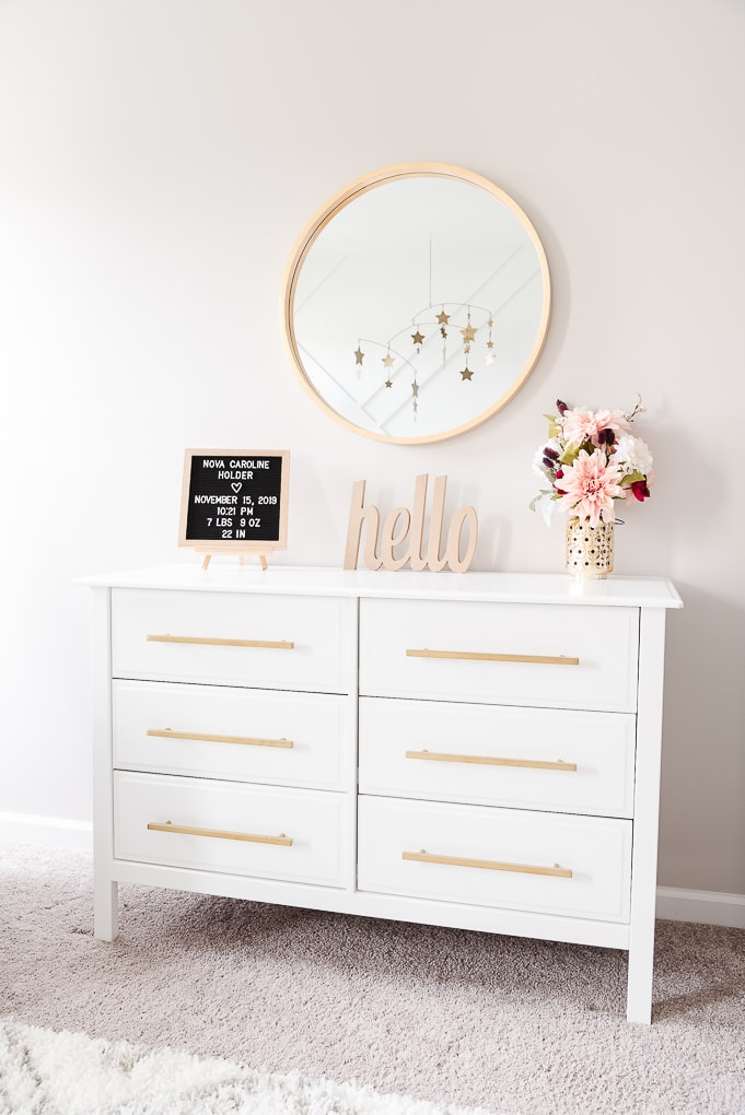 white dresser with a gold circle mirror and decorative accents on the top in a nursery