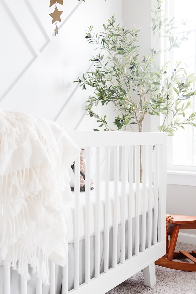 white babyletto hudson crib in a nursery with a white blanket draped over the edge