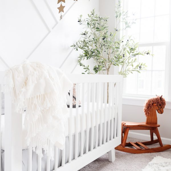 wooden rocking horse next to a white crib in a nursery with a faux olive tree in the background