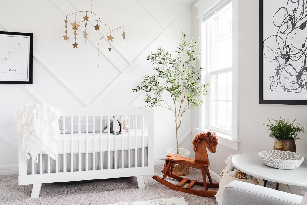 white crib and wooden rocking horse in front of a white modern accent wall in a nursery