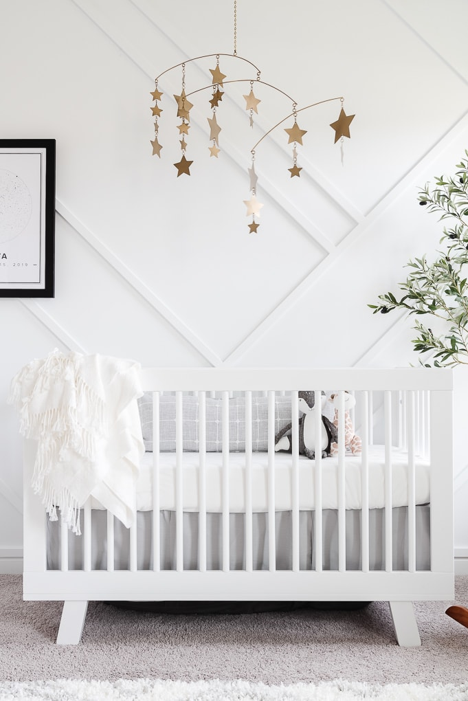 white babyletto hudson crib against a modern accent wall in a neutral nursery