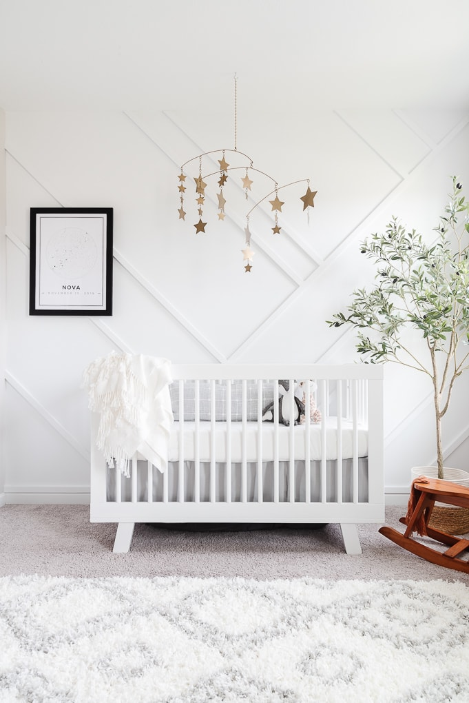 modern neutral nursery with a white crib and gold accents