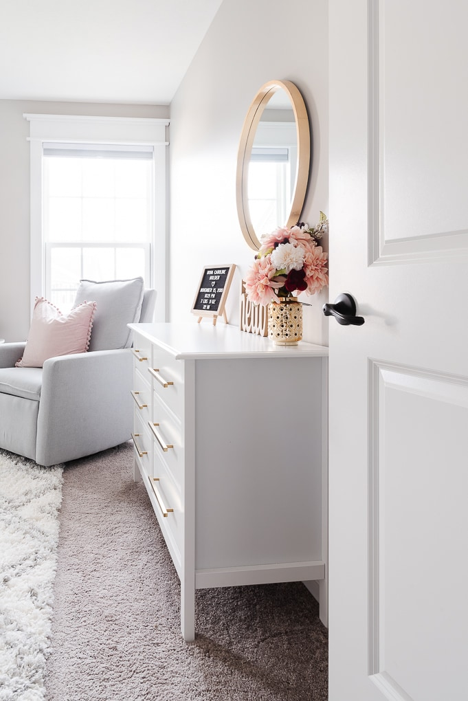 view walking through the door into a neutral feminine nursery