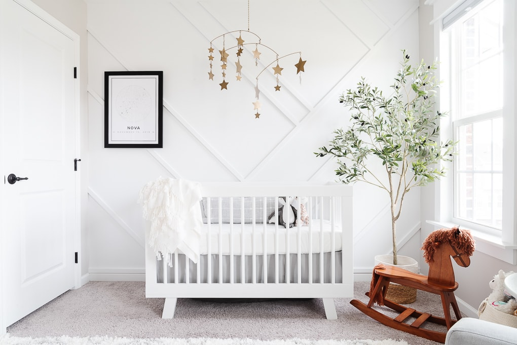 modern neutral nursery with a white crib against a white accent wall and gold accents