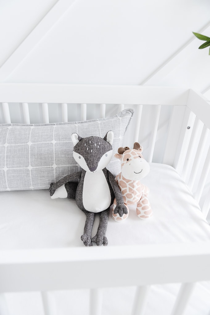 stuffed animals inside of a white drib with white sheets and a gray pillow