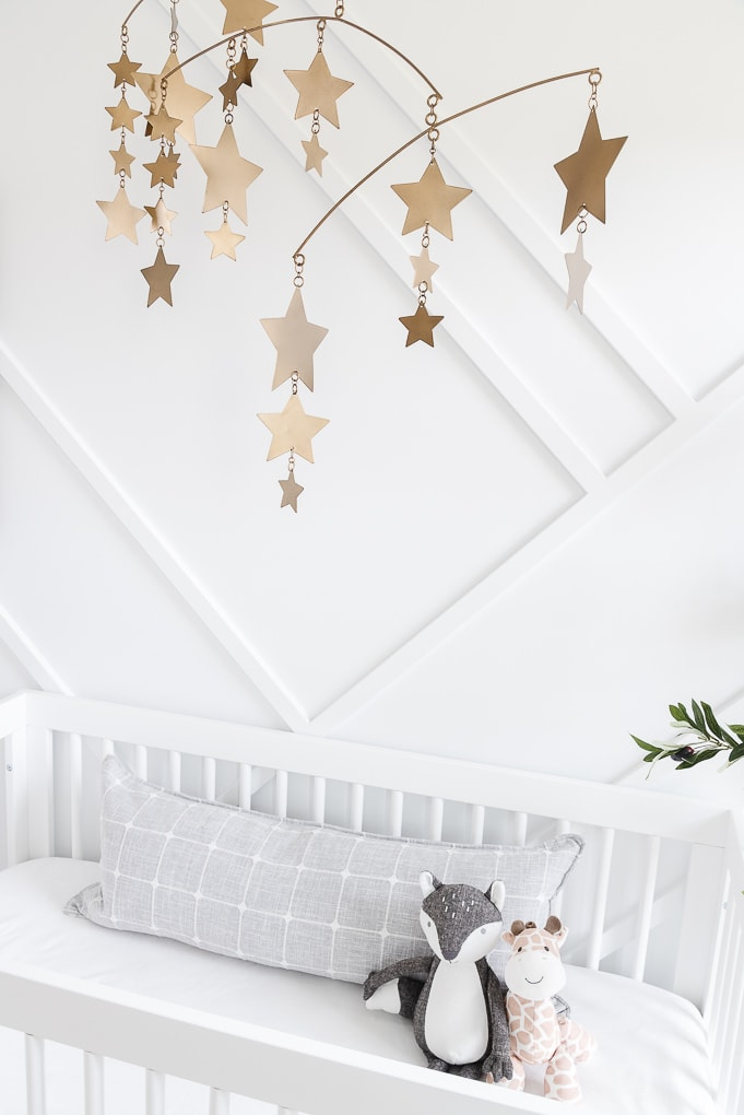 stuffed animals inside a crib in a modern nursery with a white accent wall