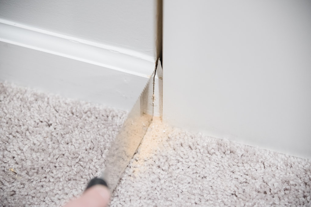 removing baseboard trim from a wall with a handsaw