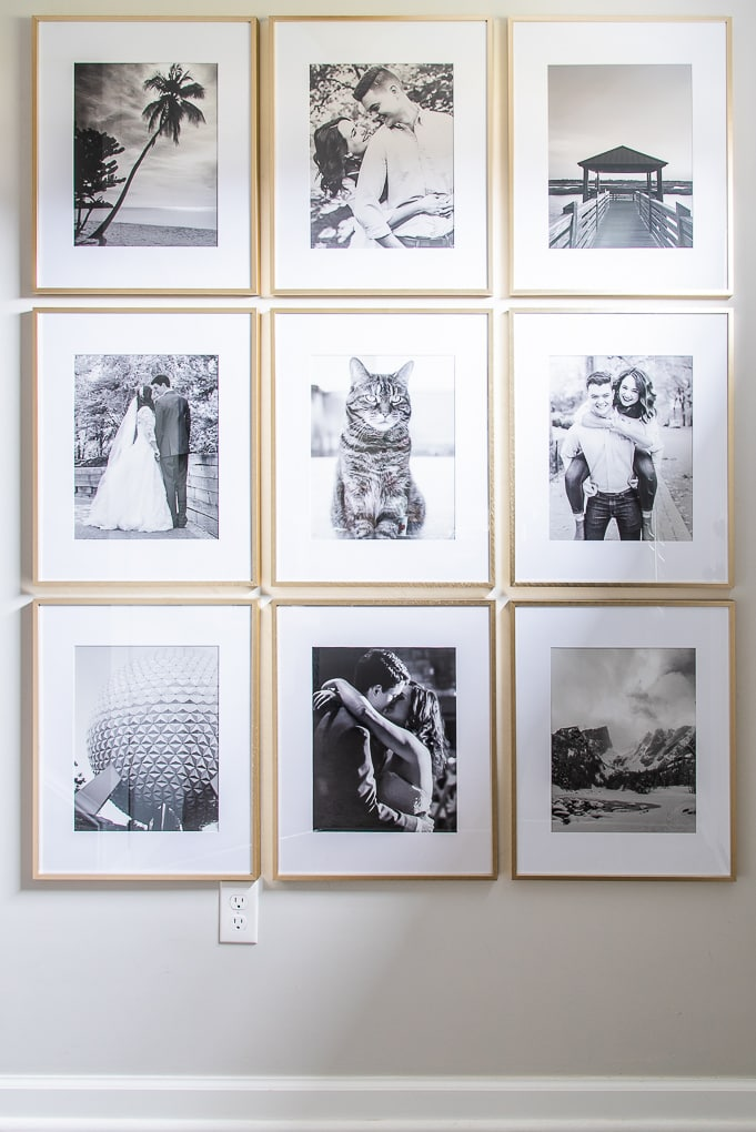 modern gallery wall with black and white photos and gold frames