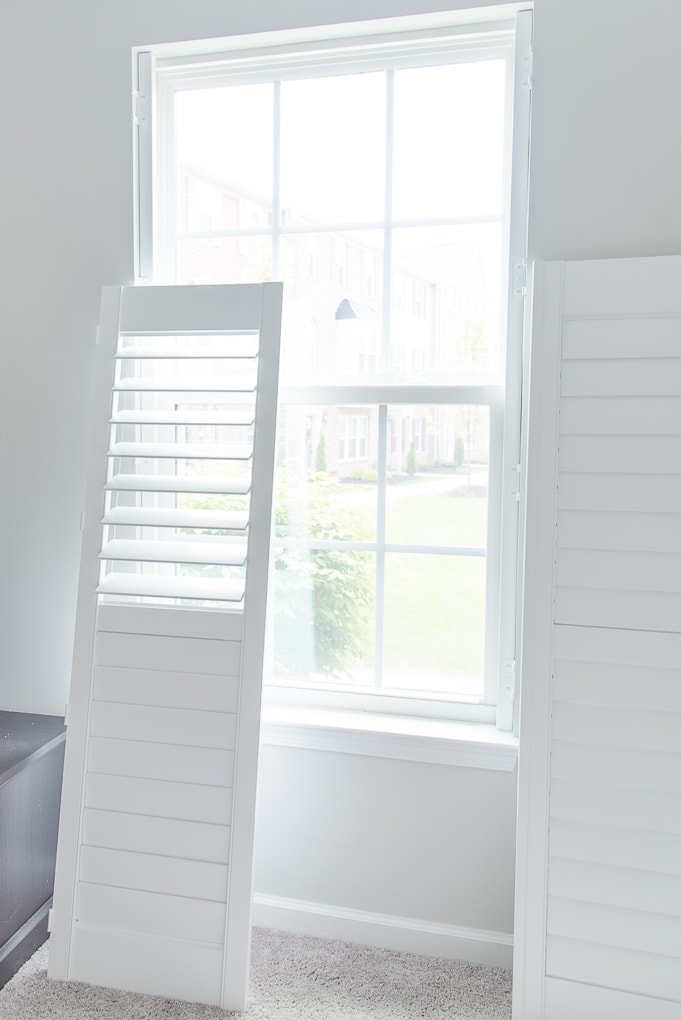 white plantation shutters next to a window before install with louvers open