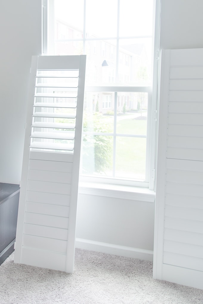 white plantation shutters next to a window before install