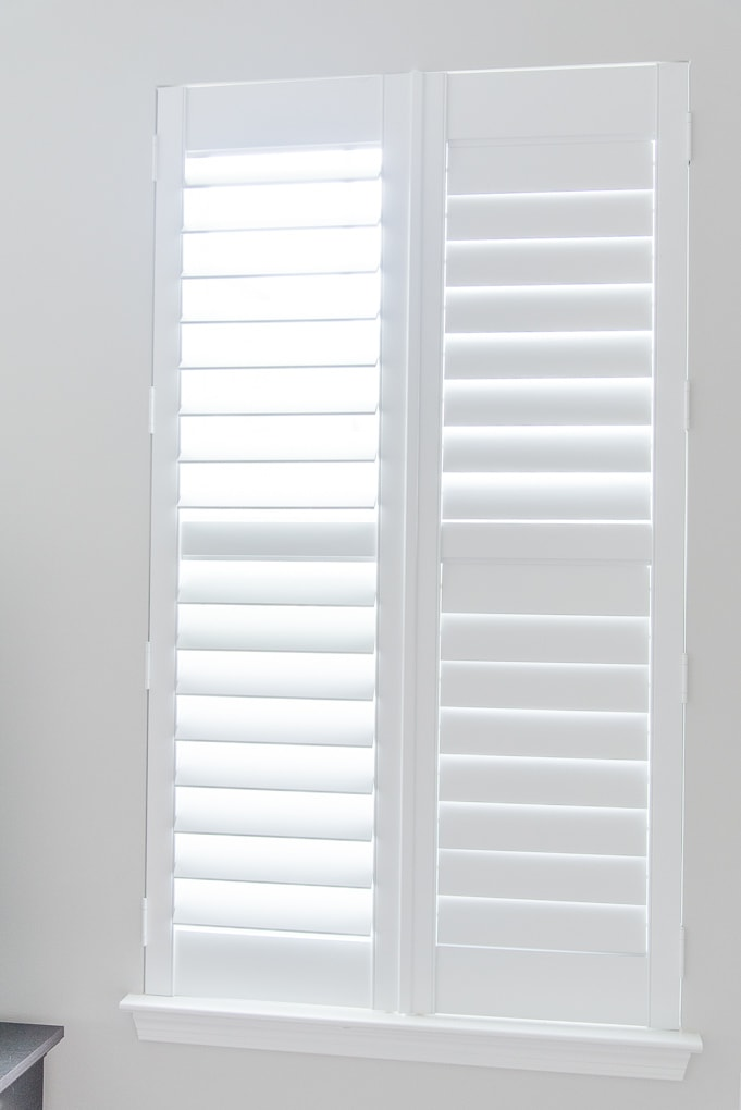 white plantation shutters closed on a window with some louvers opened
