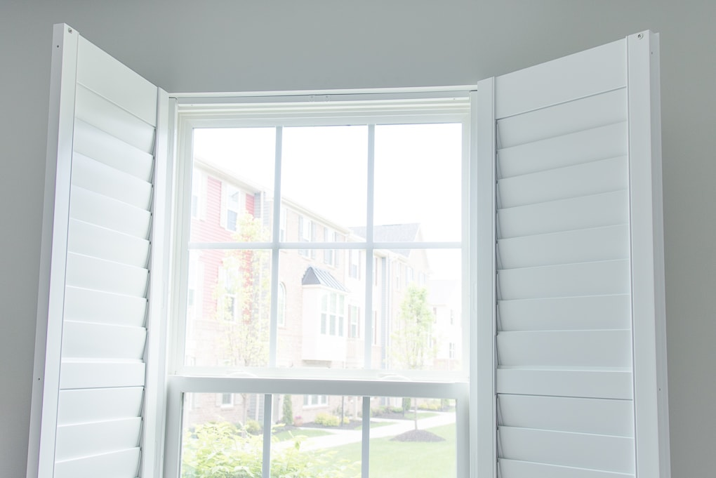 white plantation shutters open with a magnetic strip
