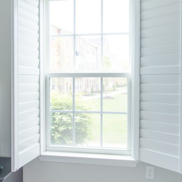 white plantation shutters open on a window