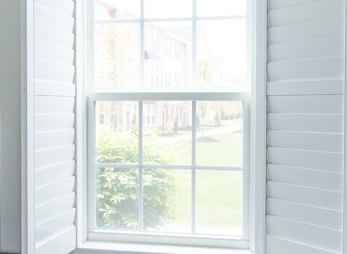 white plantation shutters open on a window