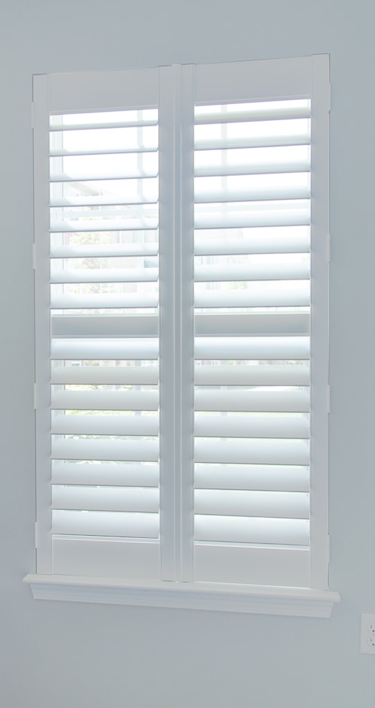 white plantation shutters closed on a window