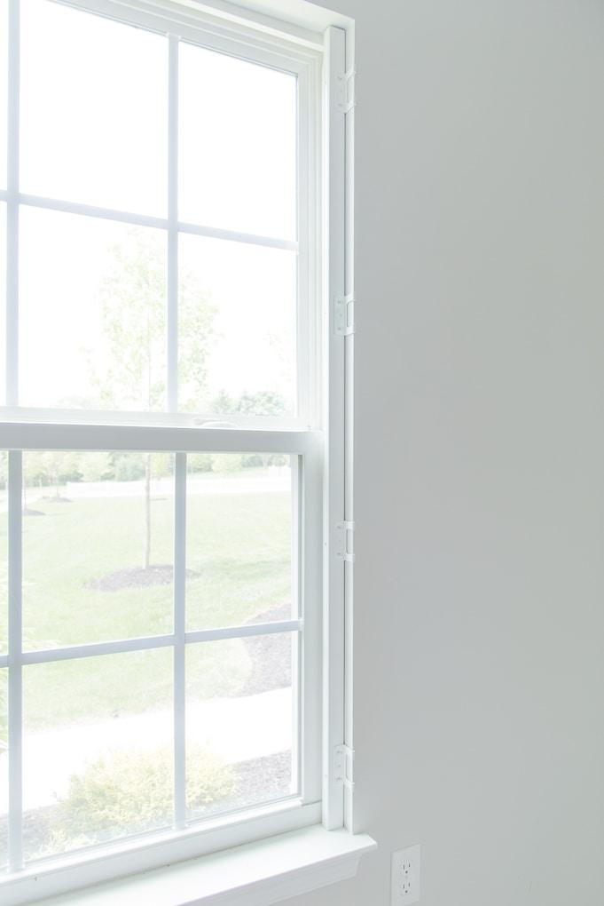 window frame with plantation shutter hardware installed