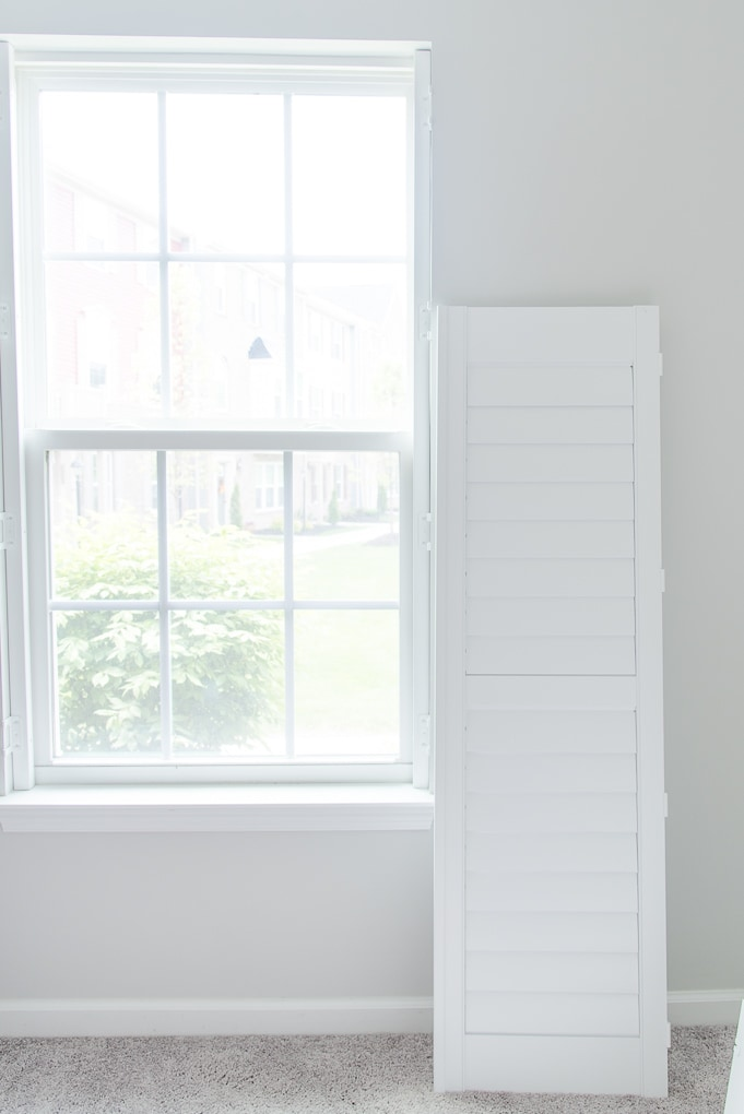 white plantation shutters next to a window before install single shutter
