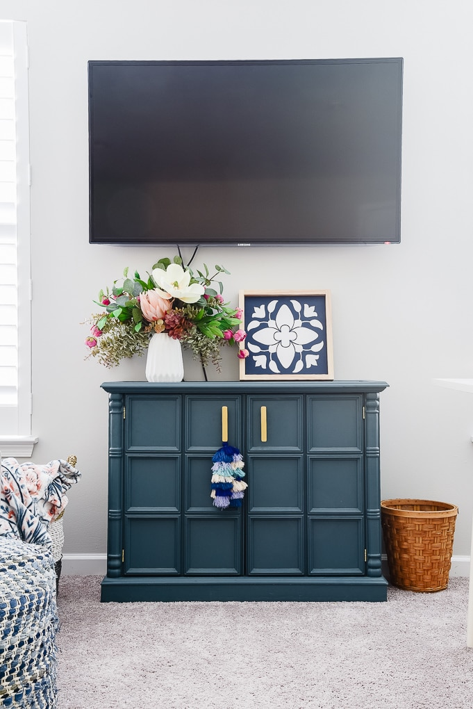 blue cabinet with tv mounted on the wall