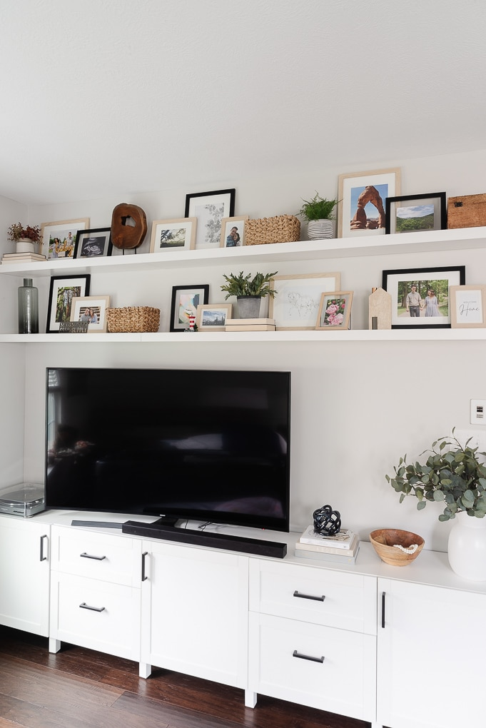 living room media center with floating shelves above the tv decorated with picture frames