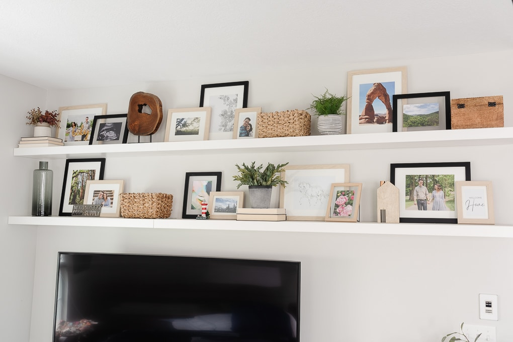 floating shelves above a tv in living room decorated with picture frames