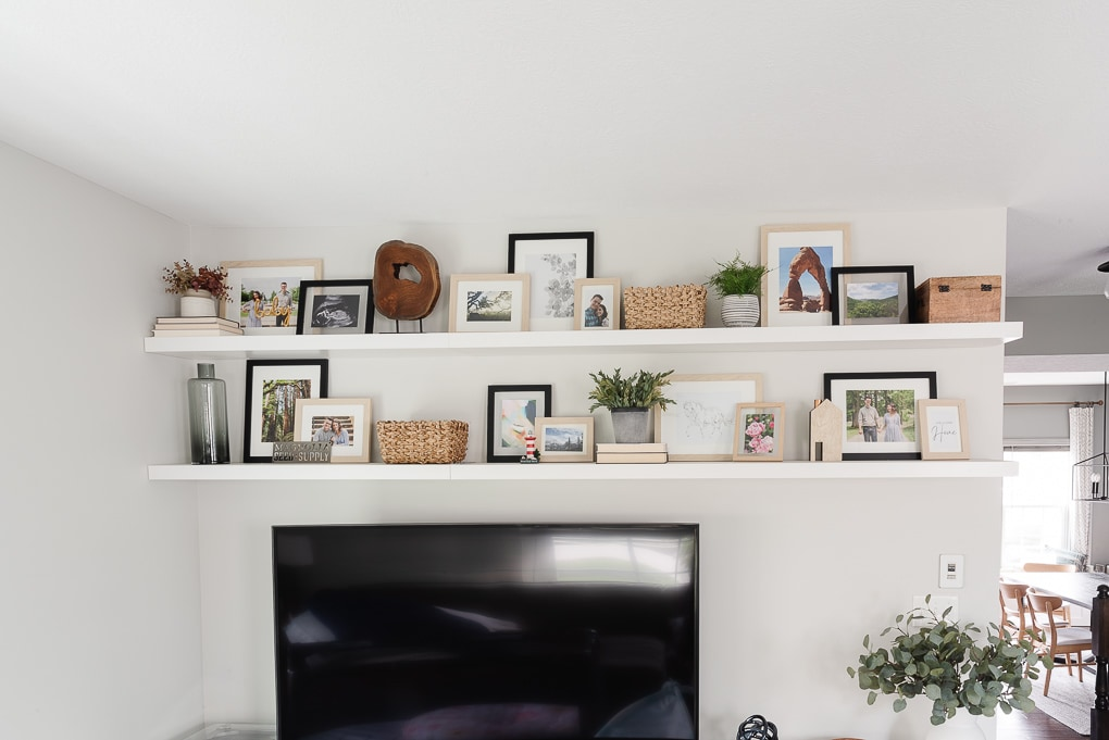 living room above tv floating shelves decorated with picture frames