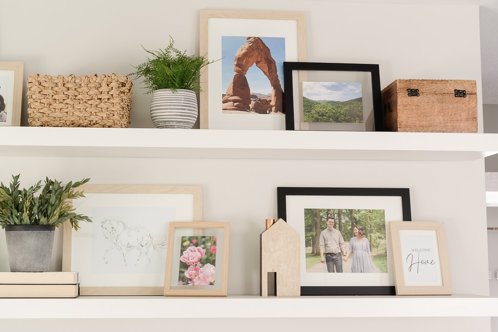floating shelves decorated with picture frames in living room