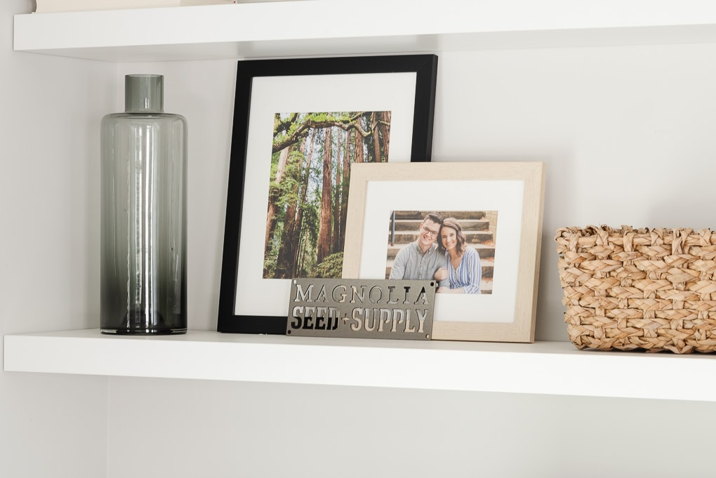 gray vase and framed family photos on white IKEA LACK floating shelf