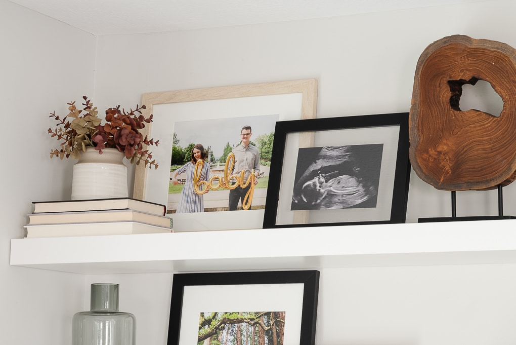 family photos framed on white IKEA LACK floating shelf
