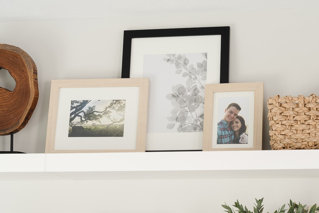 art and family photos framed on floating shelf