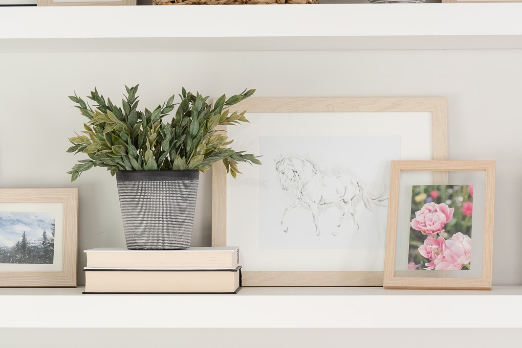 art framed on floating shelf with faux plant decor