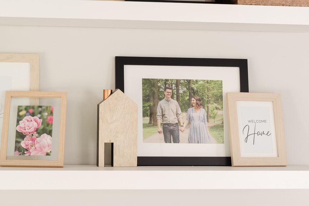 family photos framed on floating shelf