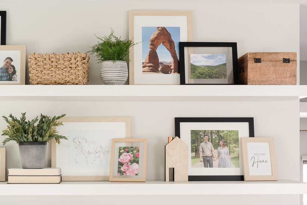 decorated white floating shelves with family photos