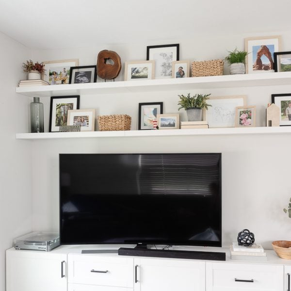 white living room media center and white floating shelves decorated