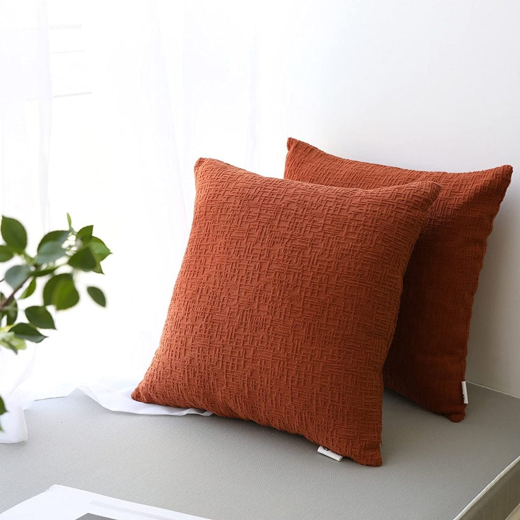 burnt orange pillow covers on chair