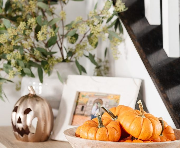 mini pumpkins in a wooden bowl with greenery and pumpkin in the background