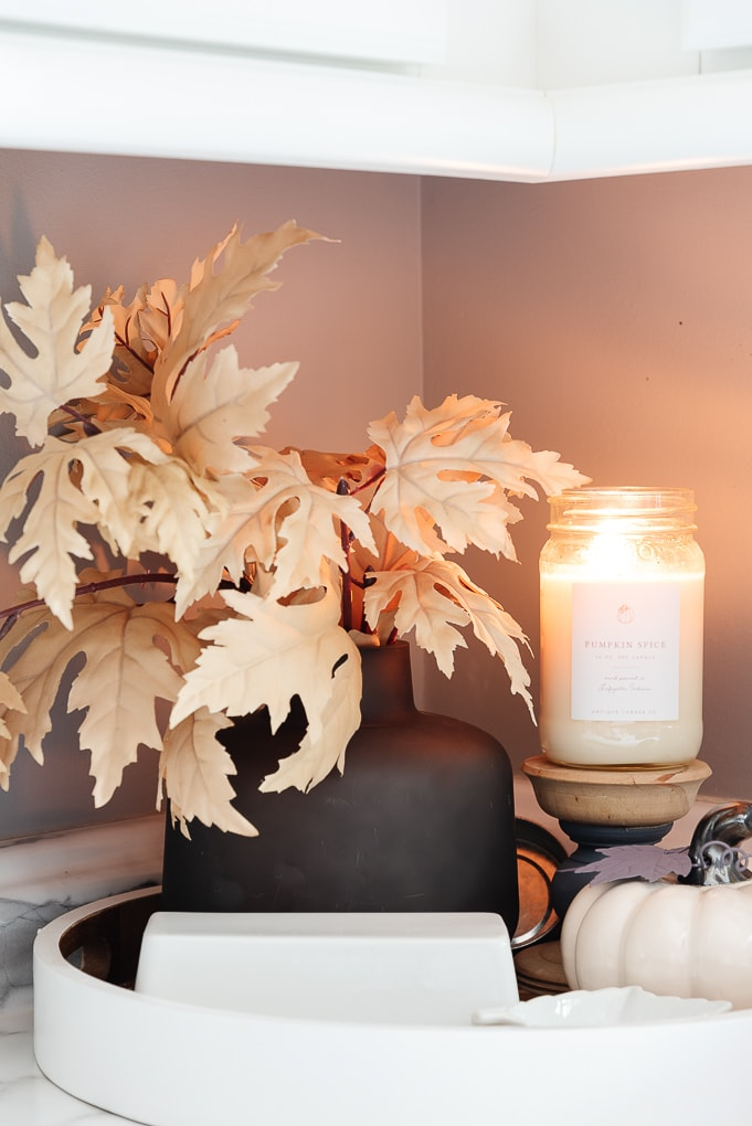 black vase with fall leaves and antique candle co candle burning in kitchen