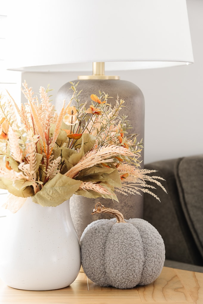 fall floral bunch in white vase with knitted gray pumpkin